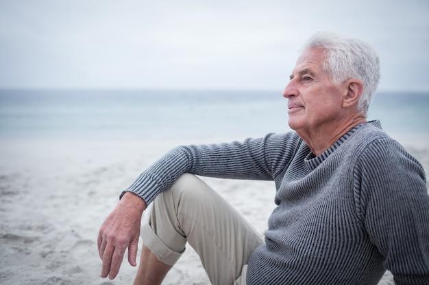 Homem aposentado pensativo, sentado na praia