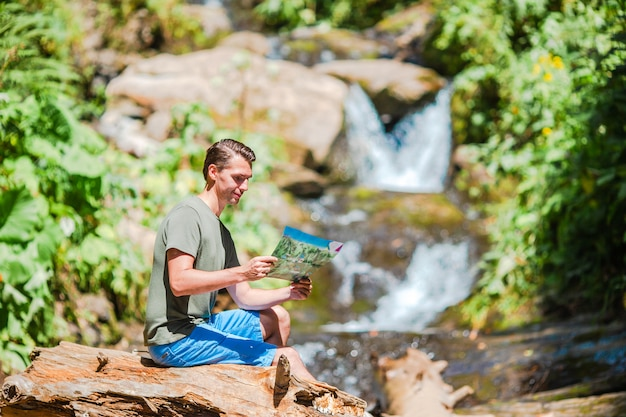 Homem apreciando a vista da cachoeira na selva