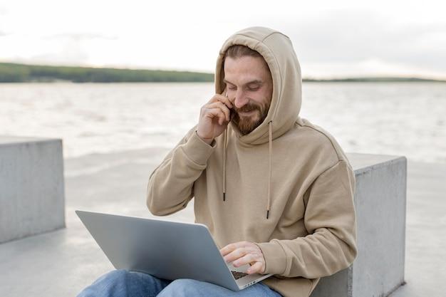 Homem apreciando o lago com laptop e smartphone