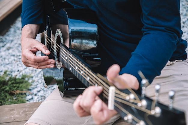 Homem aprende a tocar violão nas ruas da cidade. estilo de vida. foto de alta qualidade