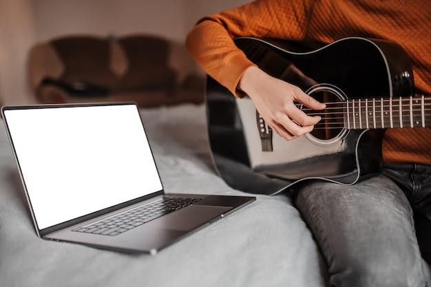 Homem aprendendo a tocar violão com a ajuda do aprendizado online em casa. cara sentado na cama com laptop e guitarra preta