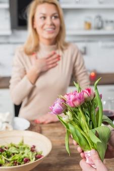 Homem, apresentando, flores, para, surpreendido, mulher, em, cozinha