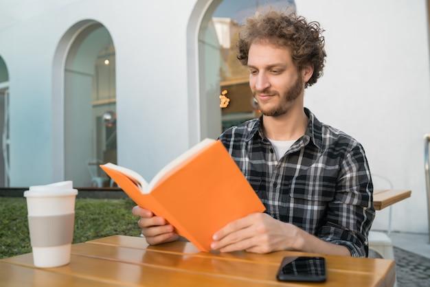 Homem, aproveitando o tempo livre e lendo um livro.