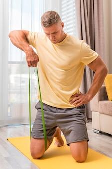 Homem apto a fazer exercício em casa com elástico