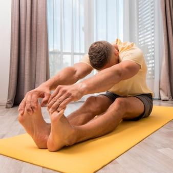 Homem apto a fazer exercício em casa no tapete
