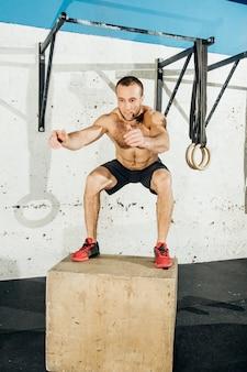 Homem apto a fazer saltos de caixa em uma academia