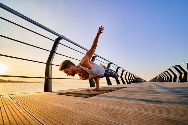 Homem apto a fazer uma parada de mão enquanto pratica ioga sozinho perto do oceano