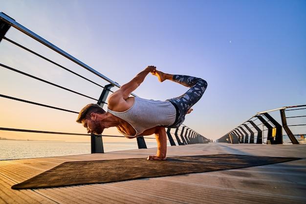 Homem apto a ficar de pé com uma mão enquanto pratica ioga sozinho perto do oceano contra o céu ao anoitecer ou amanhecer