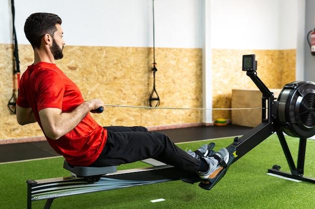 Homem apto a treinar na máquina de remo no ginásio
