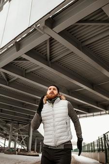 Homem apto correndo em tiro frio médio