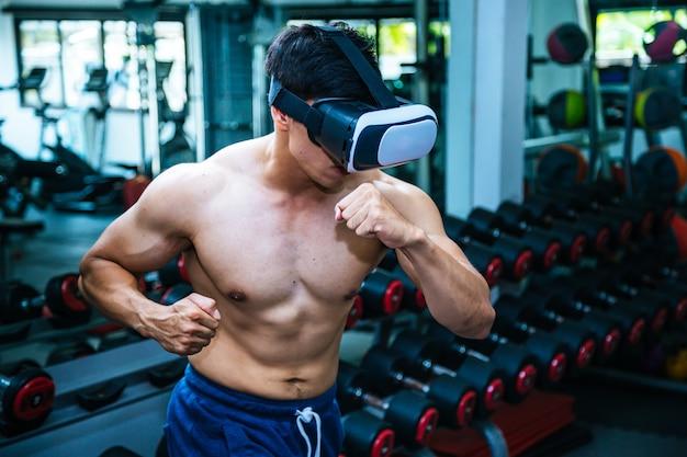 Homem apto do pugilista novo do lutador nos vidros de vr que vestem luvas de encaixotamento no treinamento.