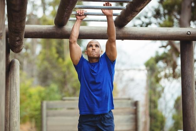 Homem apto escalando barras de macaco