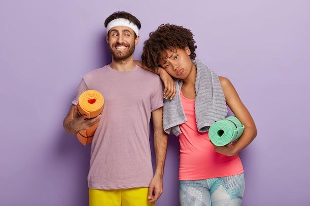 Homem apto positivo com barba por fazer carrega karemat enrolado, mulher cansada se inclina no ombro do marido, cansada após treino exaustivo, tem toalha no pescoço, passam o tempo juntos na academia. esporte