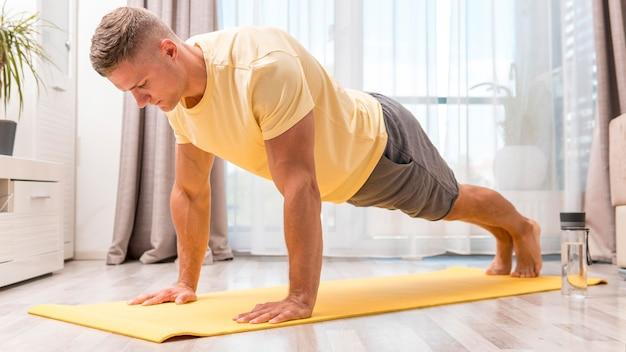 Homem apto se exercitando em casa no tatame com garrafa de água
