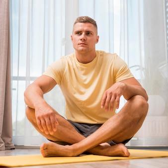 Homem apto se exercitando em casa no tatame