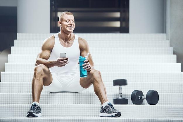 Homem apto sentado em uma escada branca com um shaker azul e alguns pesos