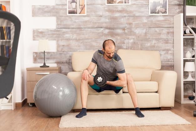 Homem apto treina seus bíceps com halteres em casa durante o auto-isolamento covid-19.