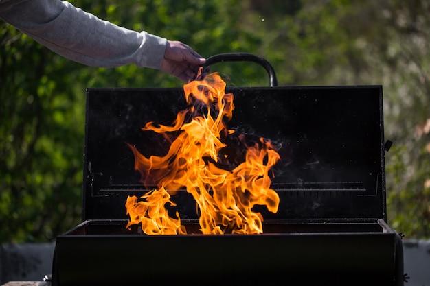 Homem aquece a churrasqueira, preparando-se para grelhar alguns tipos de carne