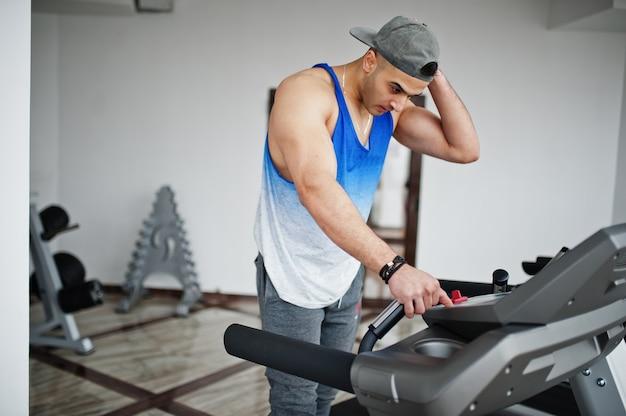 Homem árabe apto e musculoso correndo na esteira na academia.