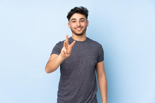 Homem árabe bonito em uma parede isolada feliz e contando três com os dedos