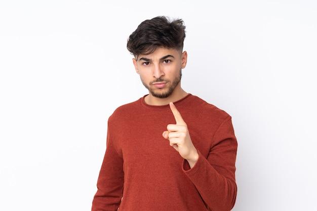 Homem árabe bonito em uma parede isolada frustrado e apontando para a frente