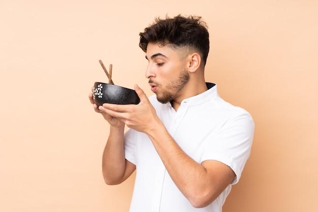 Homem árabe bonito isolado em uma parede bege segurando uma tigela de macarrão com pauzinhos e comendo