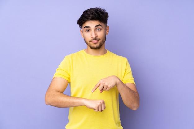 Homem árabe bonito isolado fazendo o gesto de se atrasar