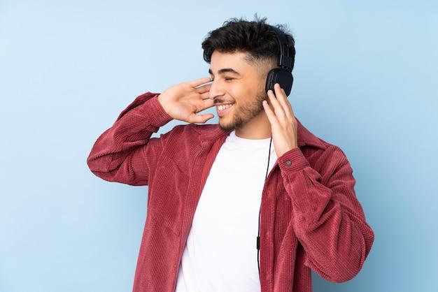 Homem árabe bonito isolado na parede azul ouvindo música e cantando