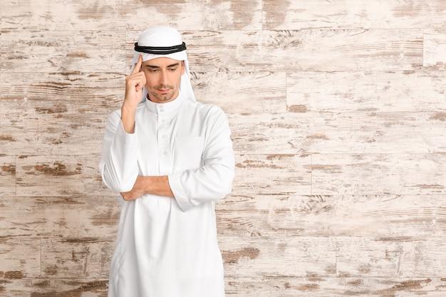 Homem árabe bonito na parede de madeira com espaço de cópia