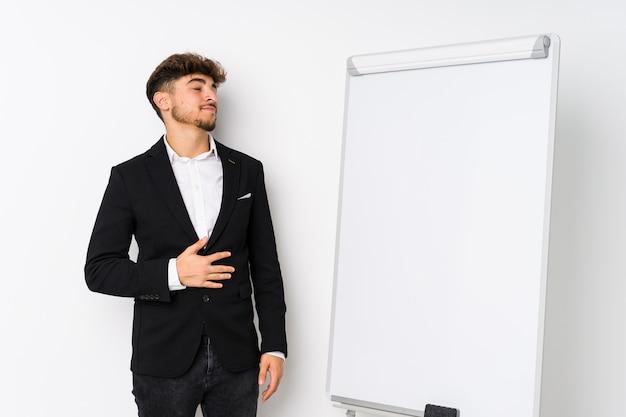 Homem árabe coaching de jovens negócios toca a barriga, sorri suavemente, conceito de comer e satisfação.