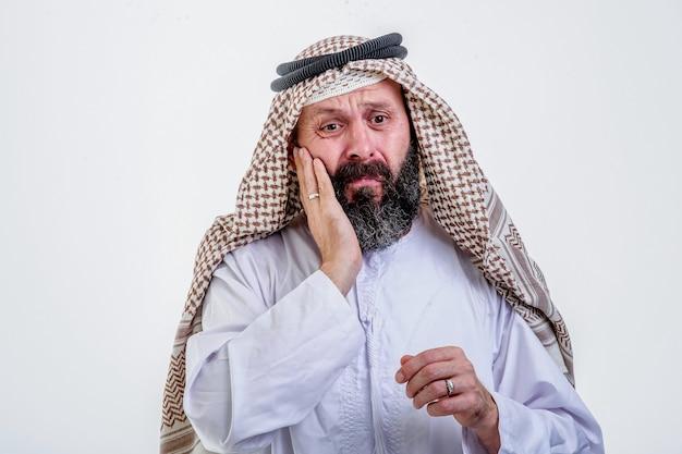 Homem árabe, colocando as duas mãos no peito, tendo um ataque cardíaco, em fundo branco.
