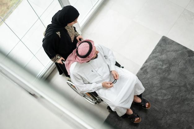 Homem árabe com cadeira de rodas em casa