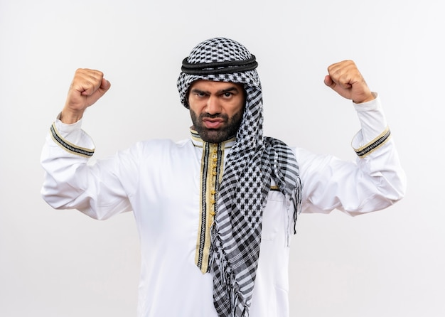 Homem árabe com roupa tradicional cerrando os punhos e levantando as mãos com rosto sério em pé sobre uma parede branca