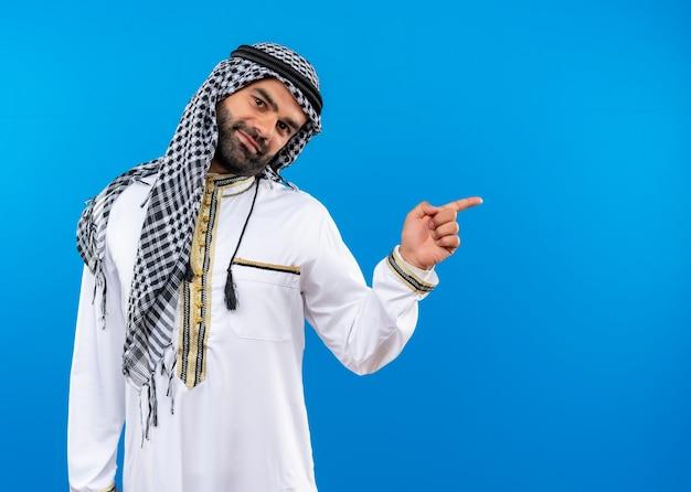 Homem árabe com roupa tradicional com sorriso no rosto apontando com o dedo para o lado em pé sobre a parede azul