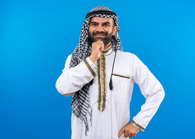 Homem árabe com roupa tradicional com sorriso no rosto positivo e feliz em pé sobre a parede azul