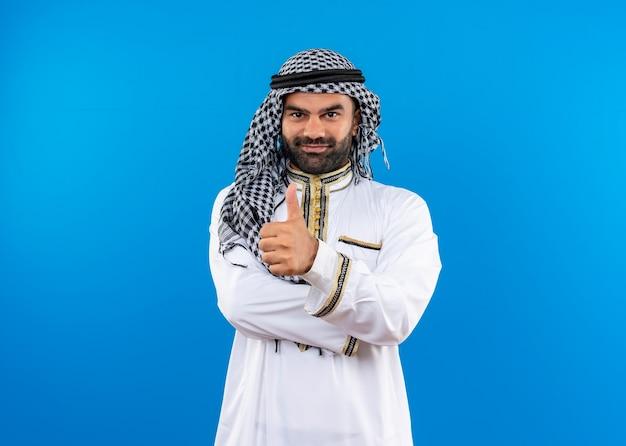Homem árabe com roupa tradicional e sorriso no rosto mostrando os polegares em pé sobre a parede azul