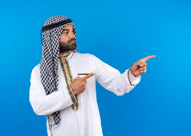 Homem árabe com roupa tradicional olhando para o lado, apontando com os dedos para o lado com rosto sério de pé sobre a parede azul