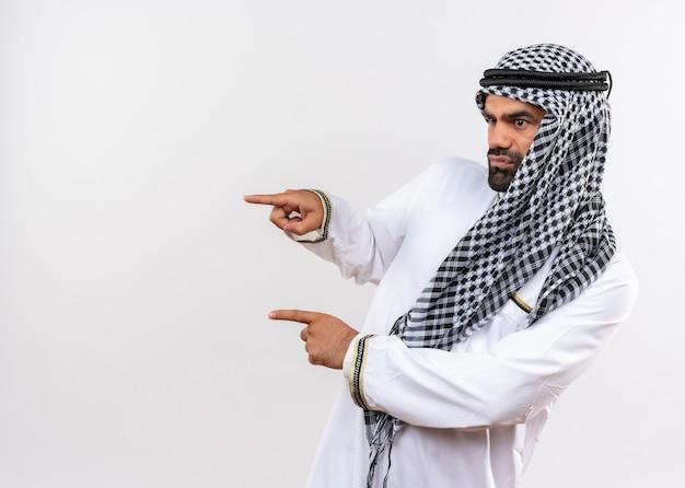 Homem árabe com roupa tradicional olhando para o lado com o rosto sério apontando com os dedos para o lado em pé sobre uma parede branca