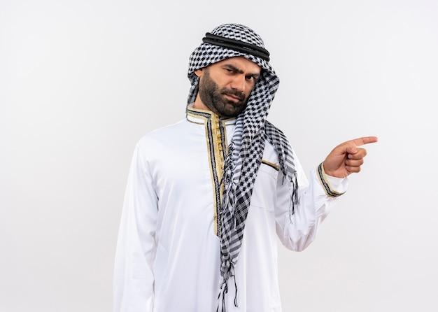Homem árabe com roupa tradicional, rosto carrancudo apontando com o dedo para o lado em pé sobre uma parede branca