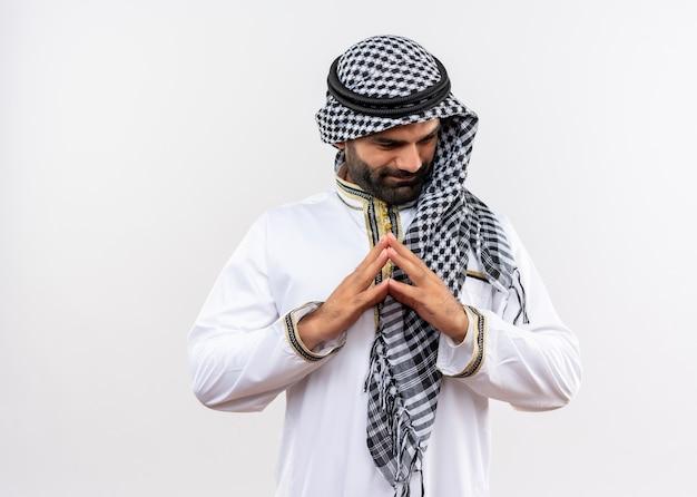 Homem árabe com roupa tradicional segurando as palmas das mãos juntas olhando para o lado com um sorriso no rosto em pé sobre uma parede branca
