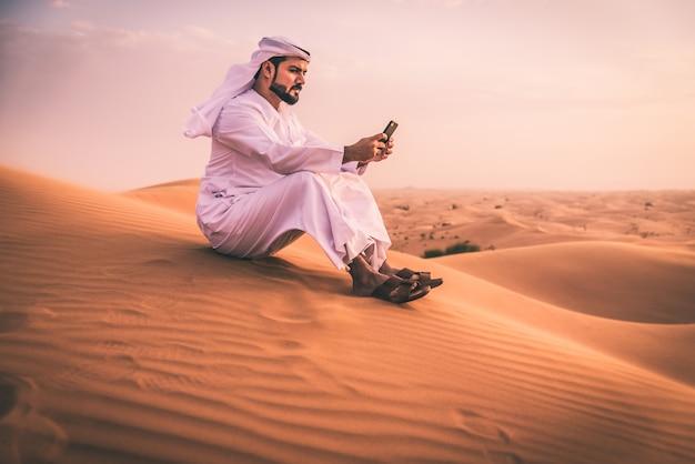 Homem árabe com roupas tradicionais dos emirados andando no deserto