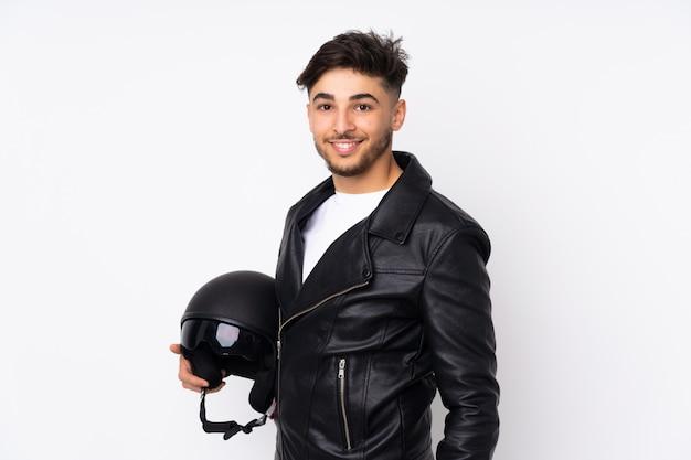 Homem árabe com um capacete de moto na parede branca, sorrindo muito