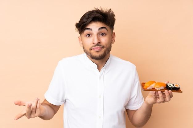 Homem árabe comendo sushi isolado em bege, fazendo gestos de dúvida enquanto levanta os ombros
