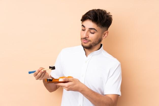 Homem árabe comendo sushi isolado em bege