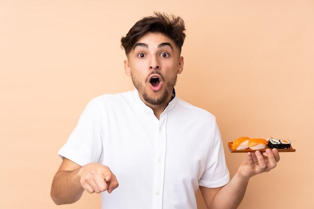 Homem árabe comendo sushi isolado em parede bege surpreso e apontando para frente