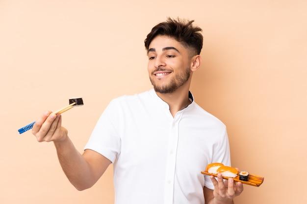 Homem árabe comendo sushi isolado em parede bege