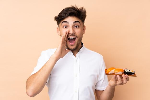 Homem árabe comendo sushi isolado na parede bege, gritando com a boca bem aberta