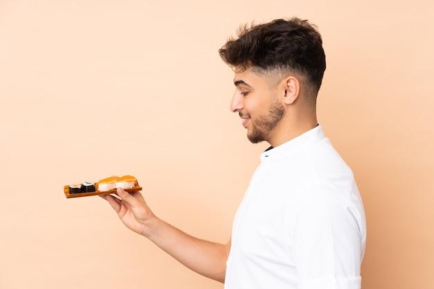 Homem árabe comendo sushi