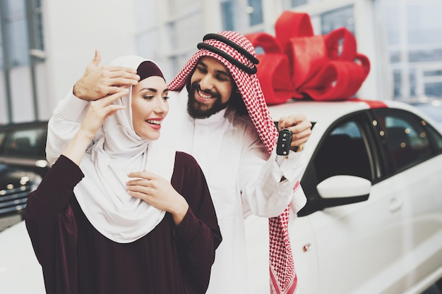 Homem árabe compra carro de presente para a bela dama em hijab.