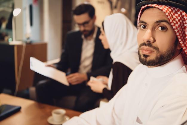 Homem árabe desanimado com esposa em psicólogo